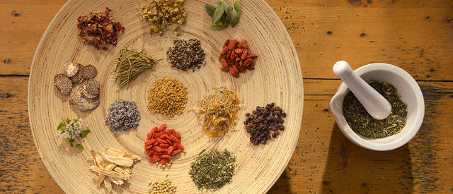 Assorted medicinal herbs and spices with a mortar and pestle --- Image by © Peter Frank/Corbis